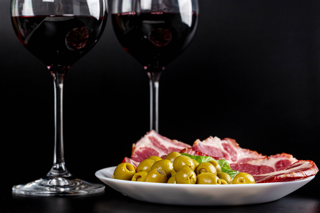 Sliced dried meat with olives and glasses of red wine