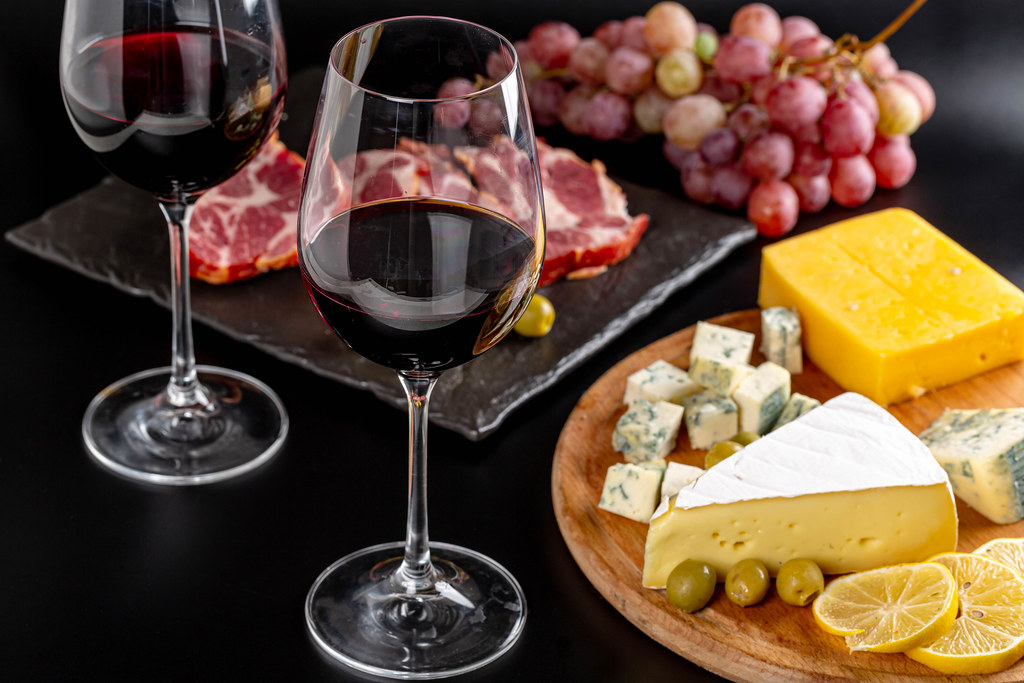 Glasses of red wine on a dark background with various delicious snacks