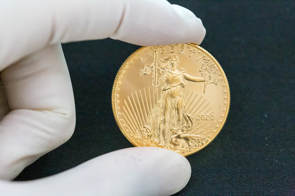 Hand with gloves holds an American Eagle Liberty 2020 gold coin