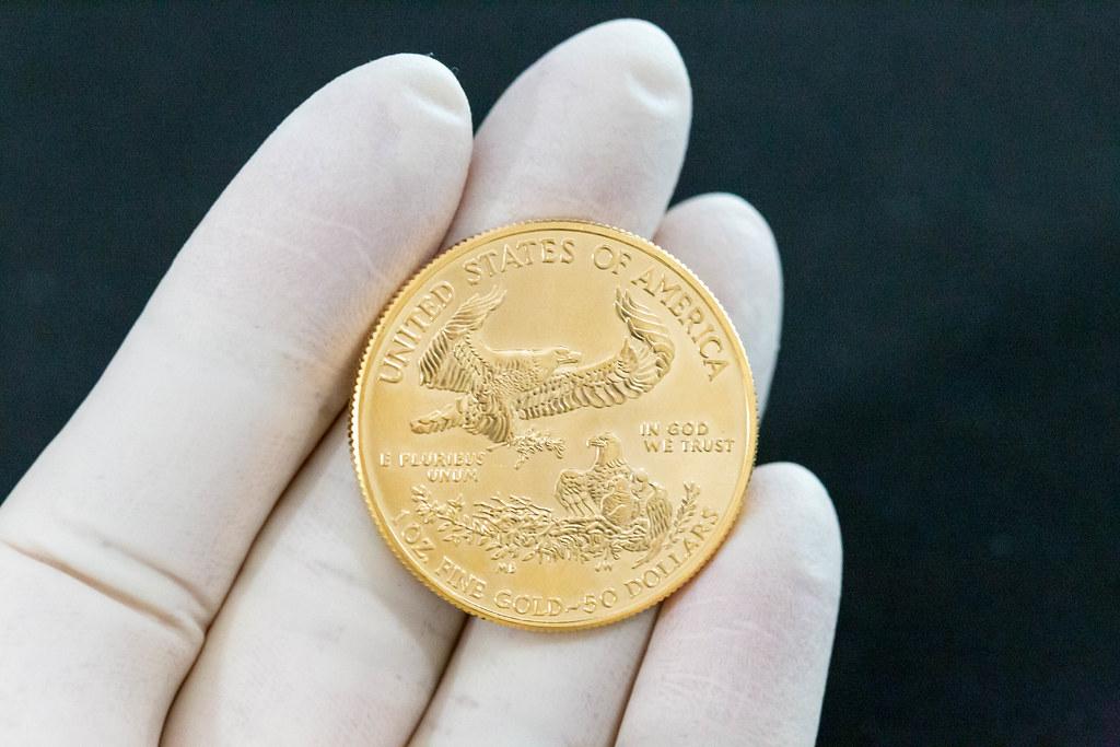 Hand mit Handschuh hält eine goldene 50 US-Dollars American Eagle 2020 Sammlermünze
