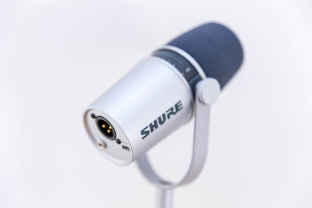 Nahaufnahme des Shure MV 7 Silver Studio-Mikrofron mit Touchpanel, Shockmount und Halterung, vor hellem Hintergrund