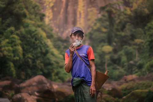 A tribal man smoking their handmade cigarette.