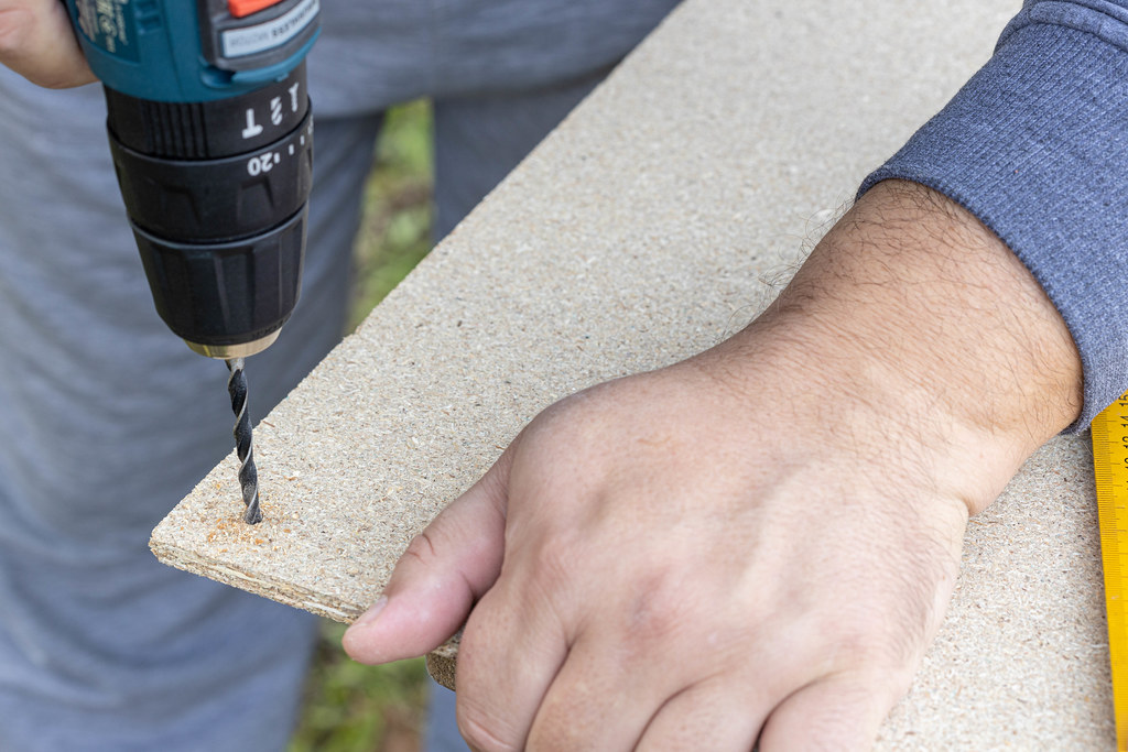 Woodworker drilling a hole on the plywood