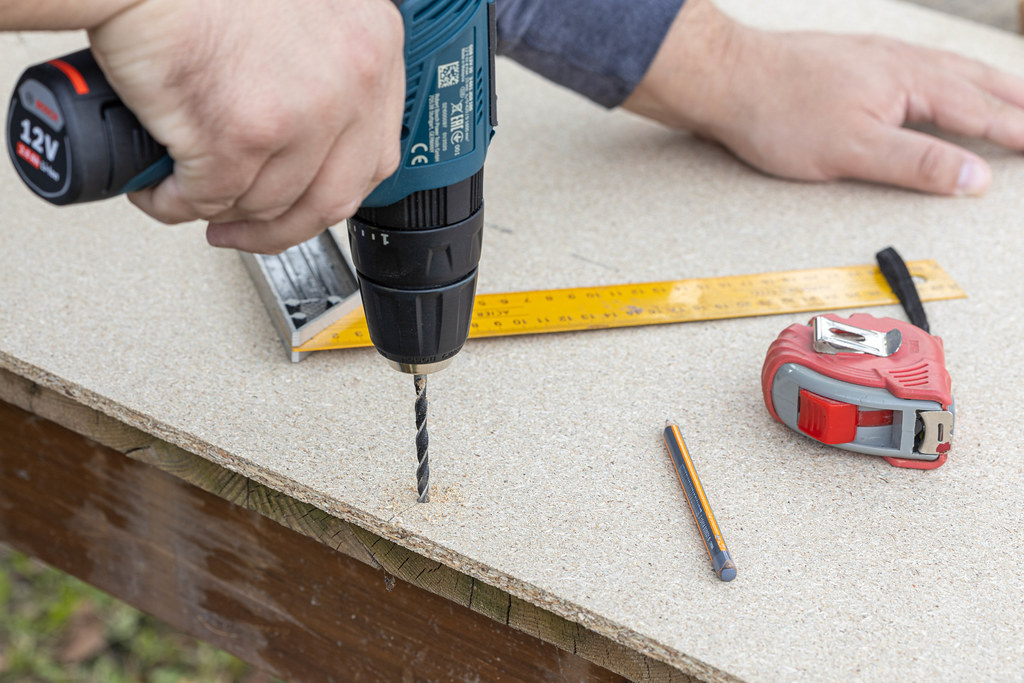 Carpenter drilling a hole in the Plywood