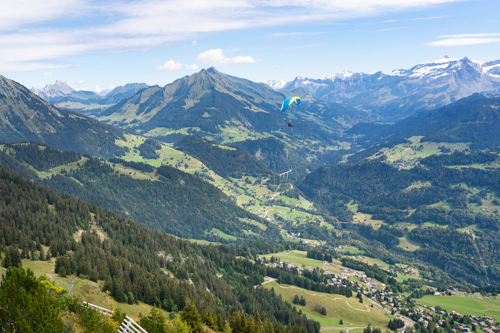 A man paragliding in Swiss mountains over a small town below