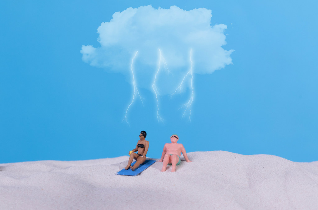 Couple in bath suit on the beach with storm cloud