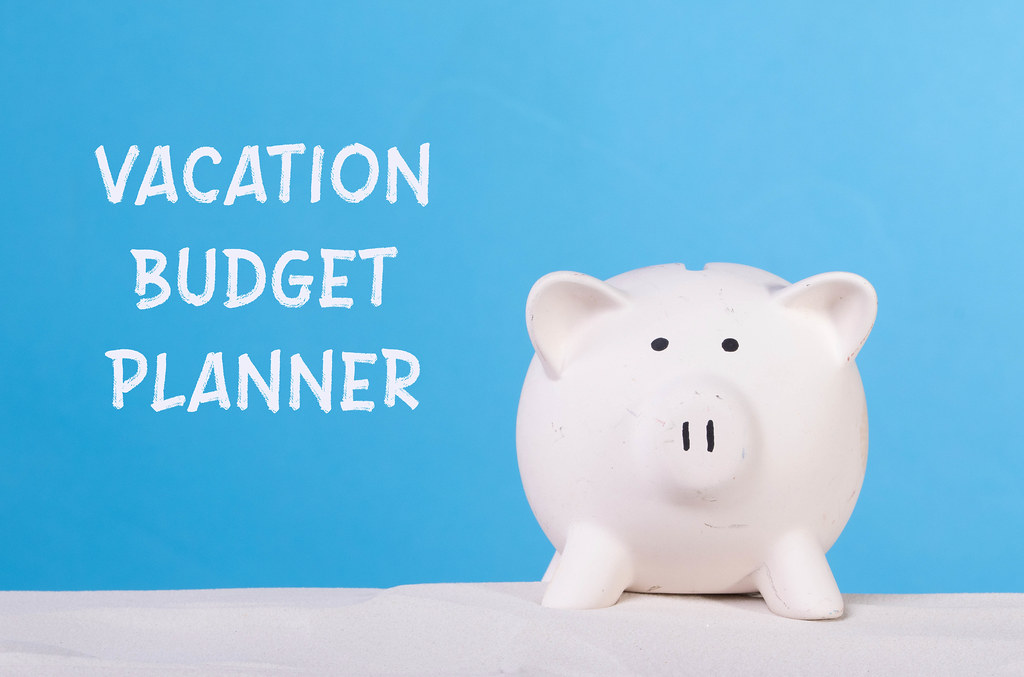 Piggy bank on sandy beach with Vacation budget planner text