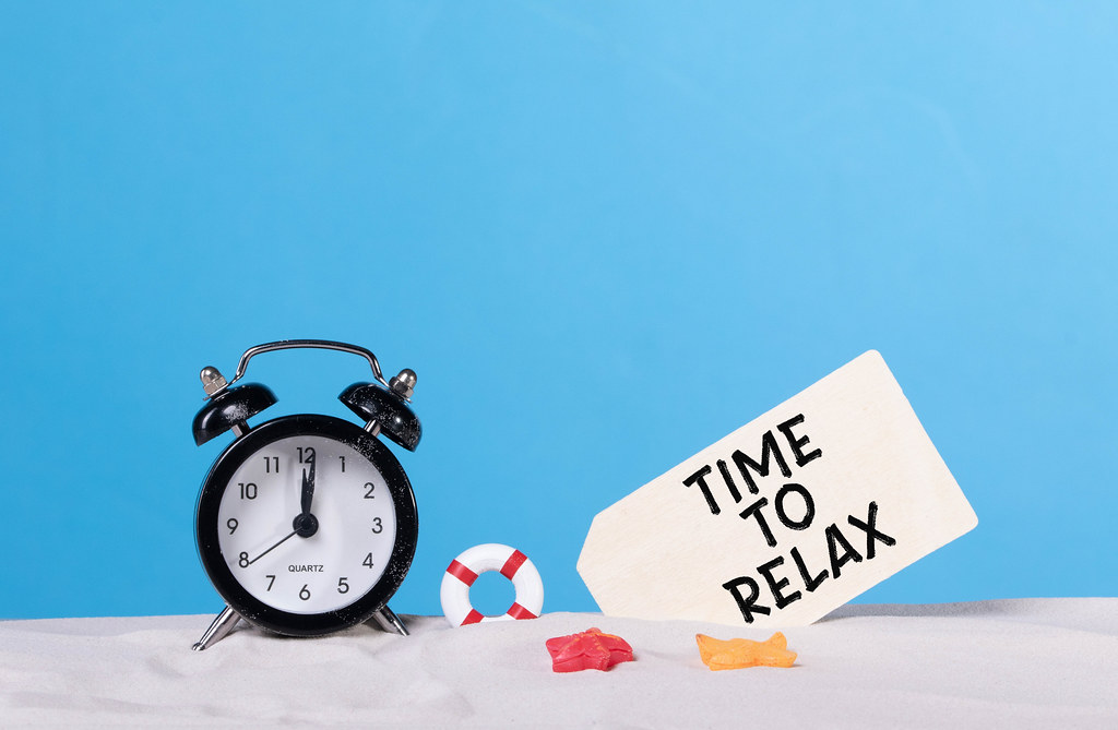 Alarm clock on the beach with Time to relax sign