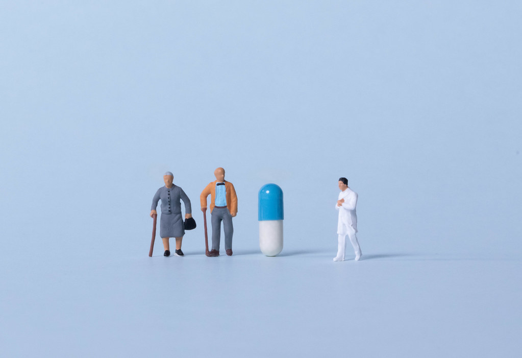 Older couple and doctor with pill on light blue background