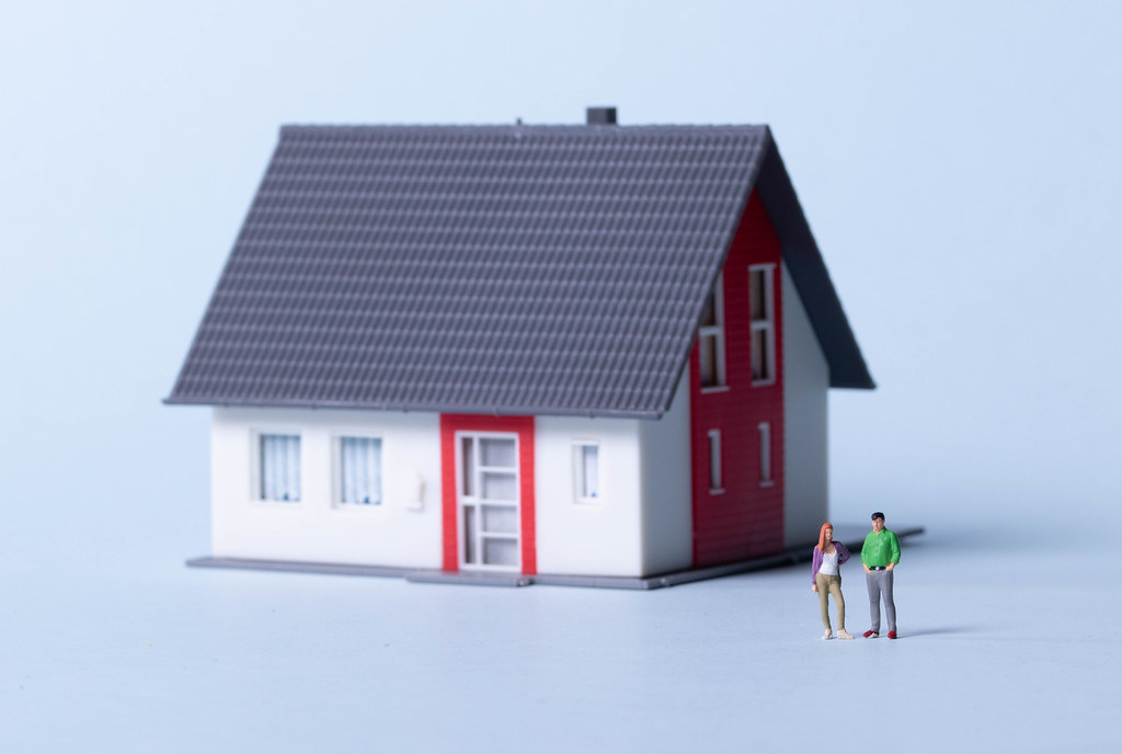 Young couple with house on a light blue background