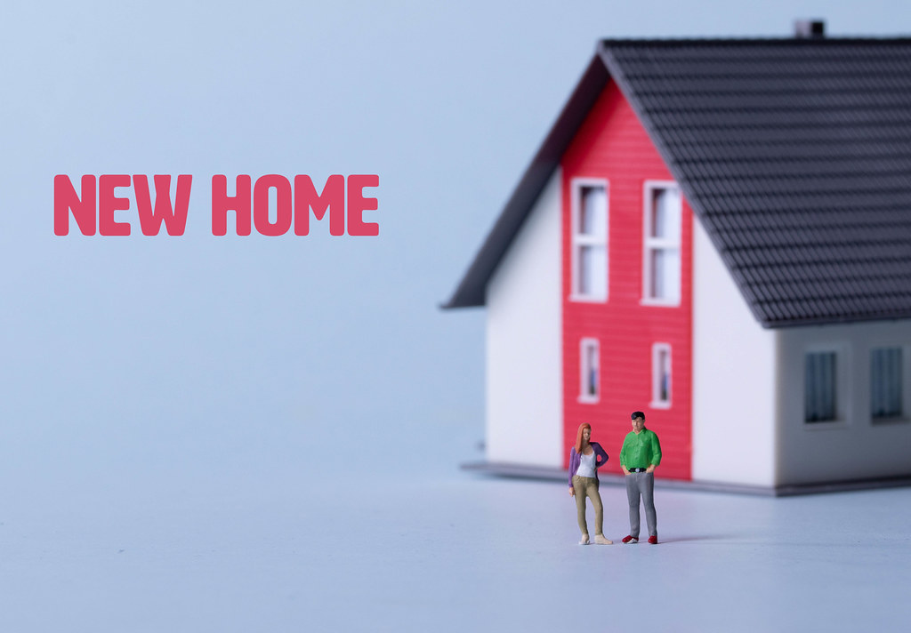 Couple standing in front of a house with New home text