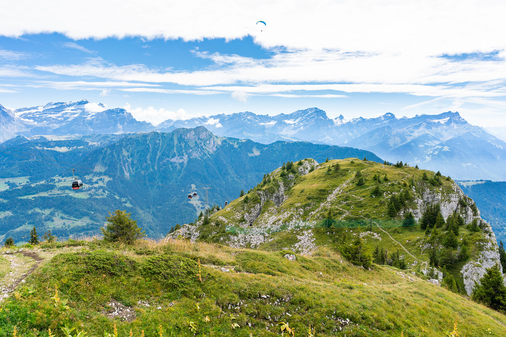 Swiss mountains hiking trail with cable carts to the side and paragliding man above