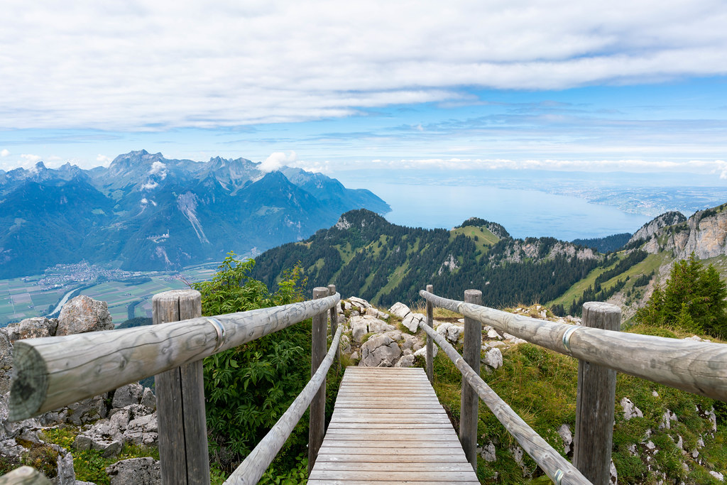Small wooden bridge on the hiking trail in Swiss Alps with the view of mountains and lake Geneva