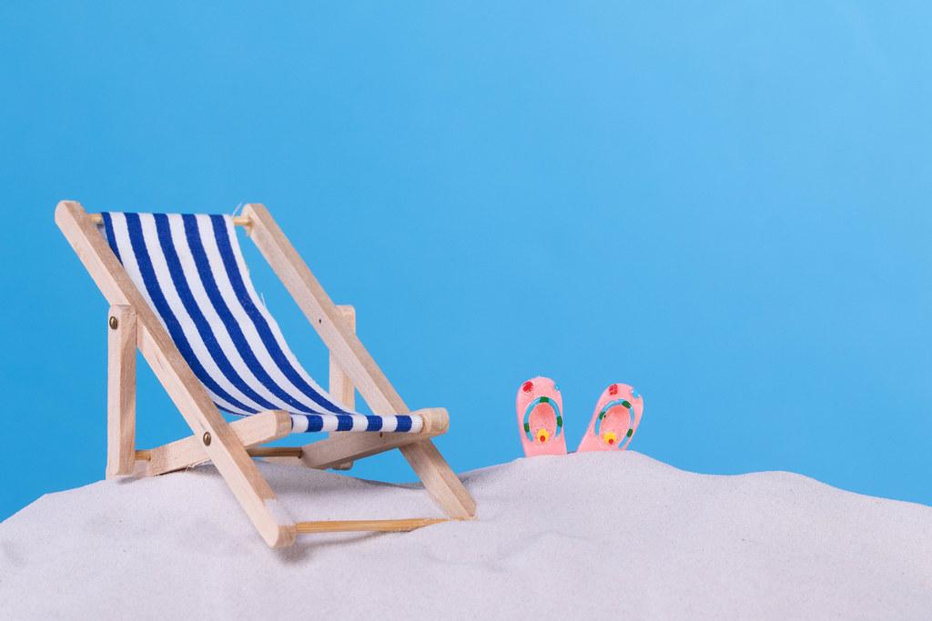 Beach chair and flip flops on the beach