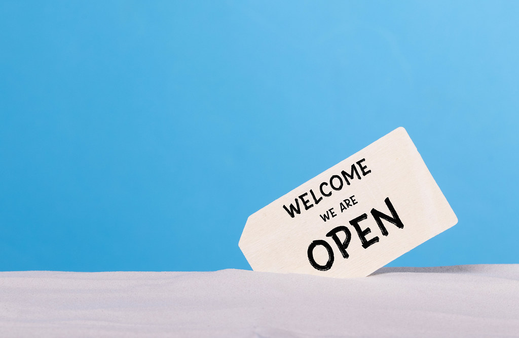 Welcome we are open sign on sandy beach