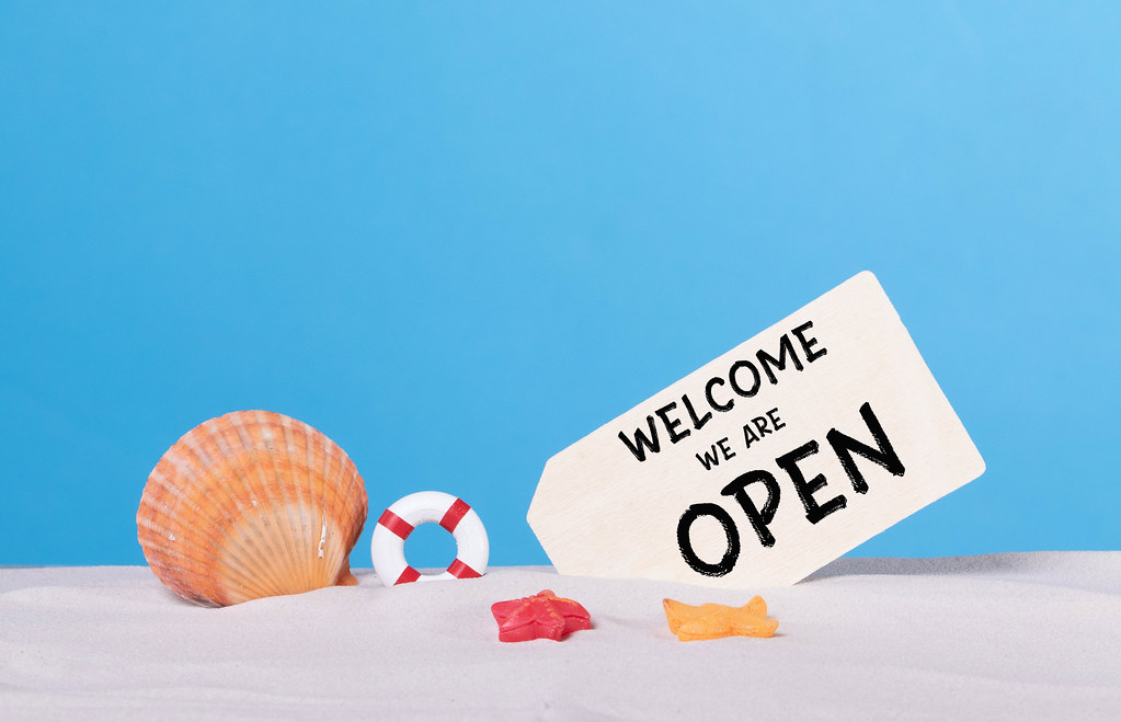 Seashells with Welcome we are open sign on sandy beach