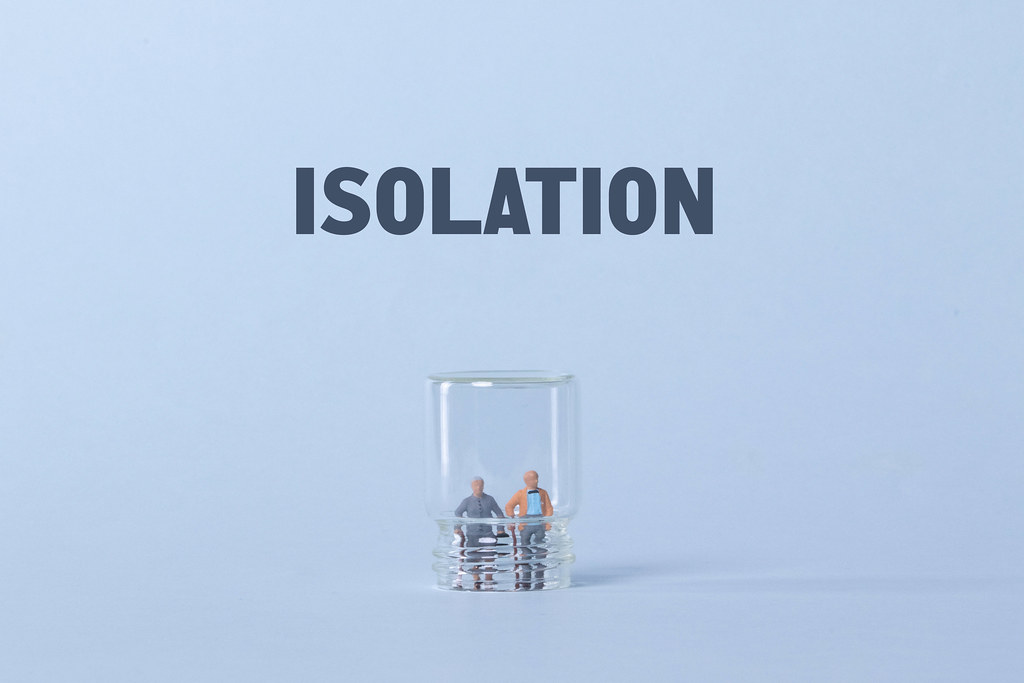 Older couple inside glass and Isolation text