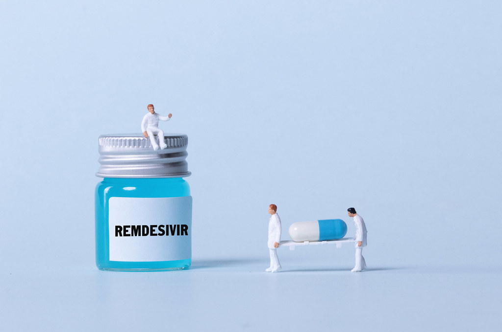 Medical workers sitting on a bottle with blue fluid and Remdesivir text