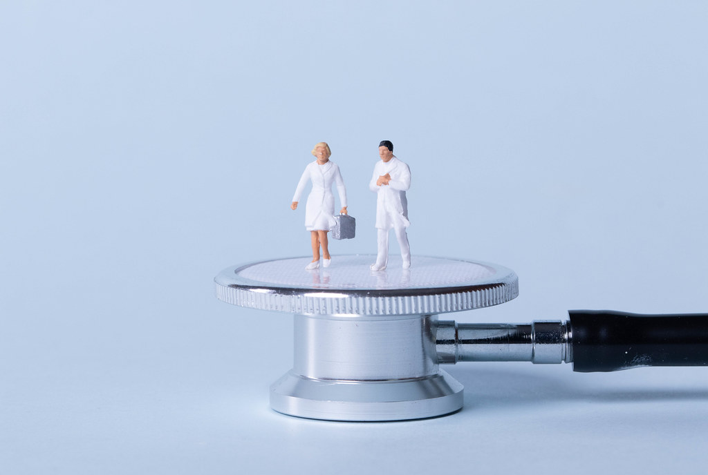 Two doctors standing on stethoscope
