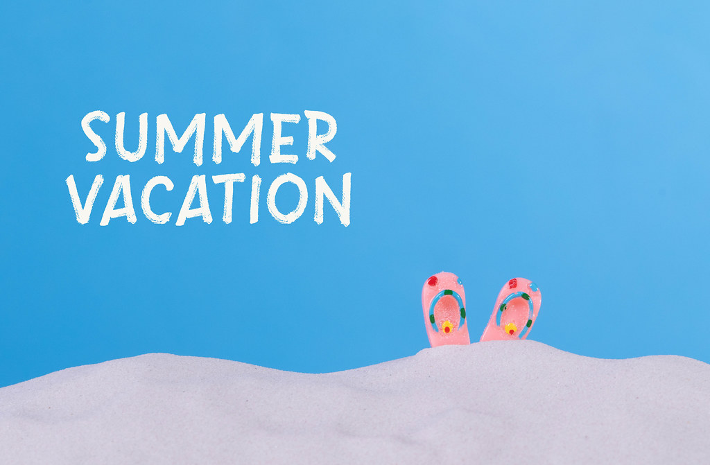 Flip flops on the beach with Summer vacation text