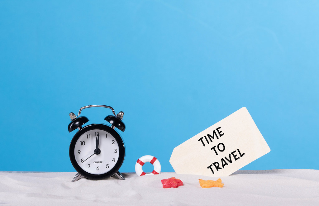 Alarm clock on the beach with Time to travel sign