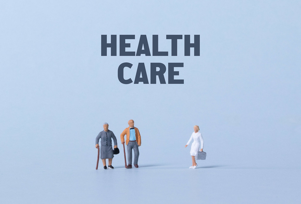 Older couple and doctor with Health care text