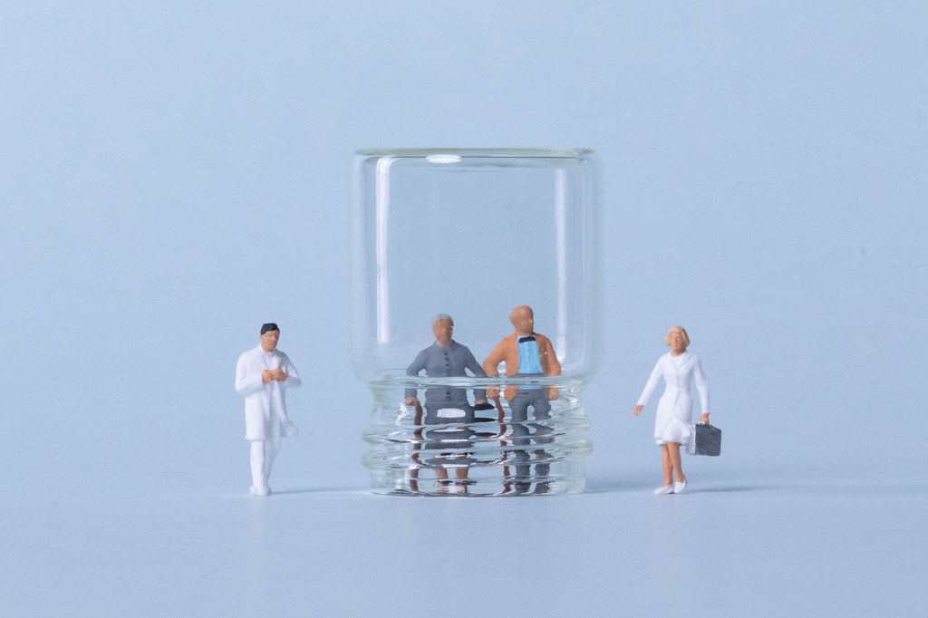 Older couple inside glass and doctors on light blue background