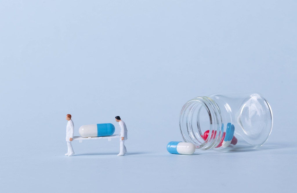 Two medical workers carrying a pills