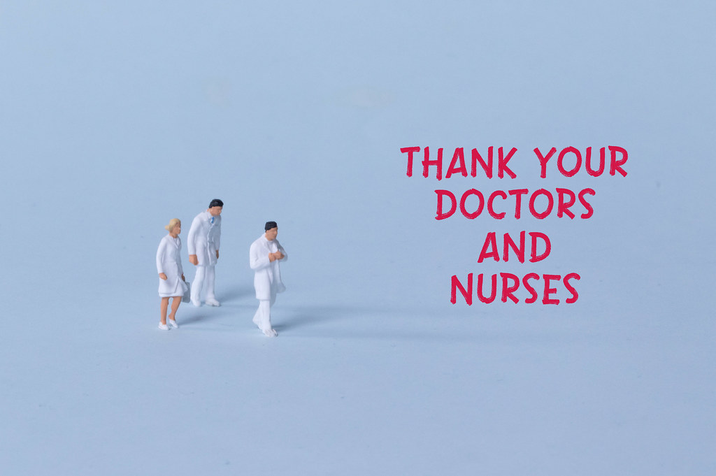 Group of doctors with red Thank you doctors and nurses text