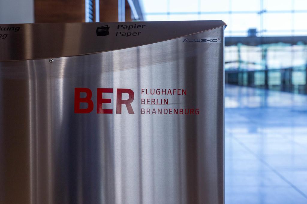 Nahaufnahme einer Mülltonne aus Metall mit BER Flughafen Berlin Brandenburg Logo in Rot