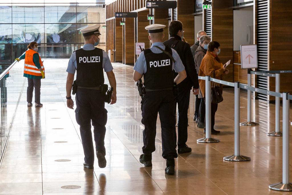 Zwei Polizisten mit Mund-Nasen Schutz während der Corona-Pandemie am neueröffneten Flughafen BER