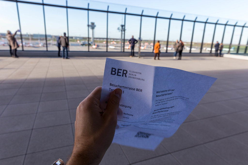 Einige Menschen beobachten die Flugzeuge aus der Besucherterrasse vom Terminal 1 am Flughafen BER