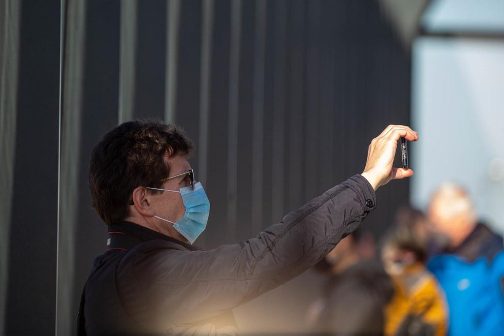 Corona-Zeit: Mann mit OP-Maske fotografiert mit seinem Smartphone am neuen Flughafen BER