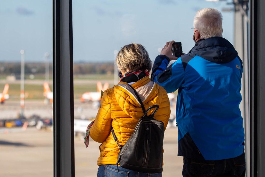 Zwei Passagiere mit Mundschutz fotografieren die Flieger aus der Flughafen BER Besucherterrasse