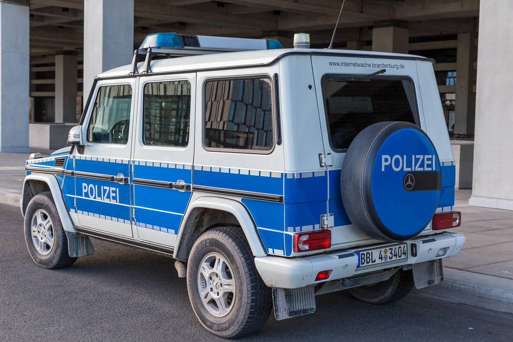 Ein großes Polizeiauto geparkt vor dem neueröffneten Flughafen BER in Berlin