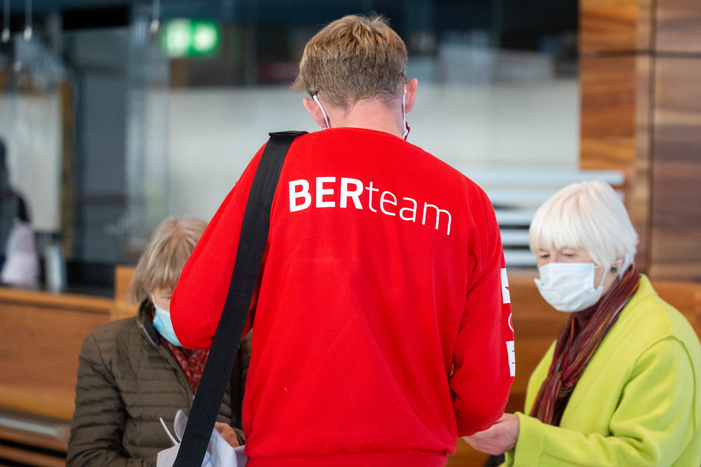 A BER airport employee wearing a red