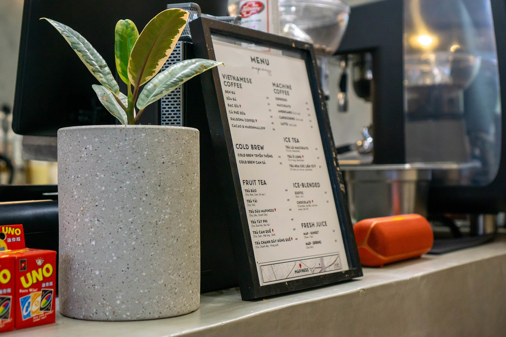 Coffee Shop Menu with many different Drinks next to Plant Pot and Speaker at a Cafe Cash Desk