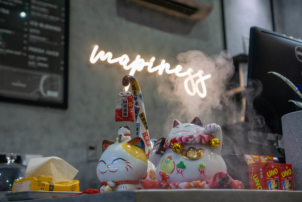 Smiling Lucky Cat with Tissues, Uno Playing Cards and Humidifier on a Cashdesk at a Cafe