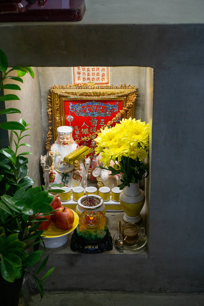 Buddhist Altar with God of Wealth, God of Land and Offerings in a Cafe in Vietnam