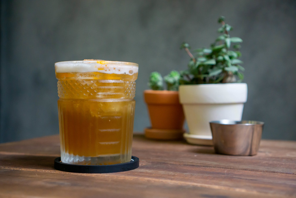 Bokeh Photo of Orange Iced Tea with Cinnamon in a Cocktail Glass with Ash Tray and Miniature Plants in the Background