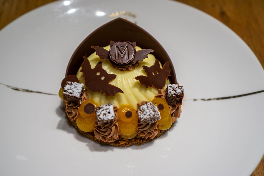 Close Up Photo of Cheesecake with Kumquat Creme and Chocolate Decorations in Halloween Design