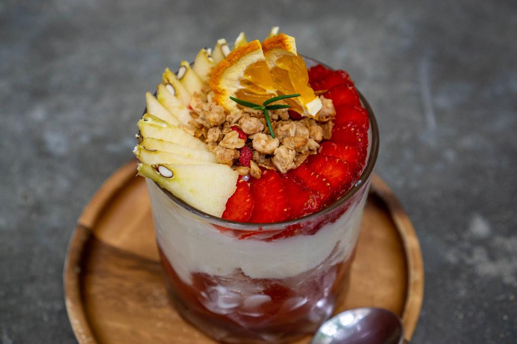 Joghurt mit Müsli, geschnittenen Äpfeln und Erdbeeren in einem Glas Nahaufnahme