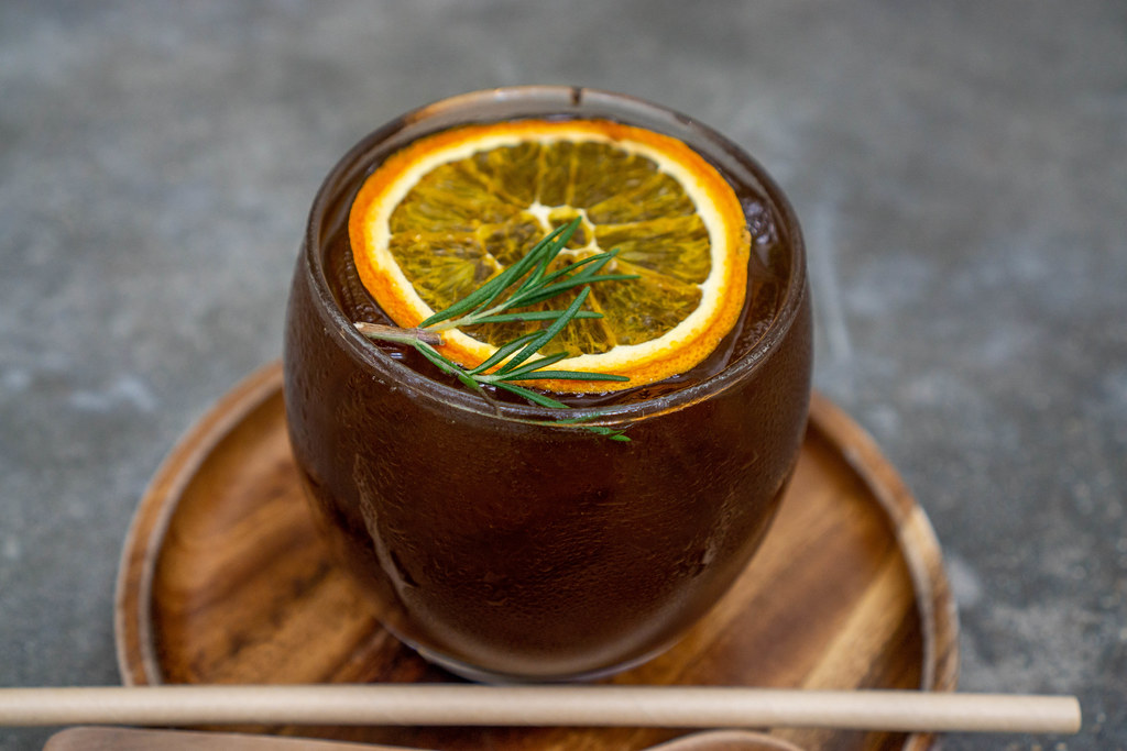 Close Up of Burnt Orange Cold Brew Coffee with Slice of Orange and Rosemary on a Wooden Plate with Paper Straw and Wooden Spoon