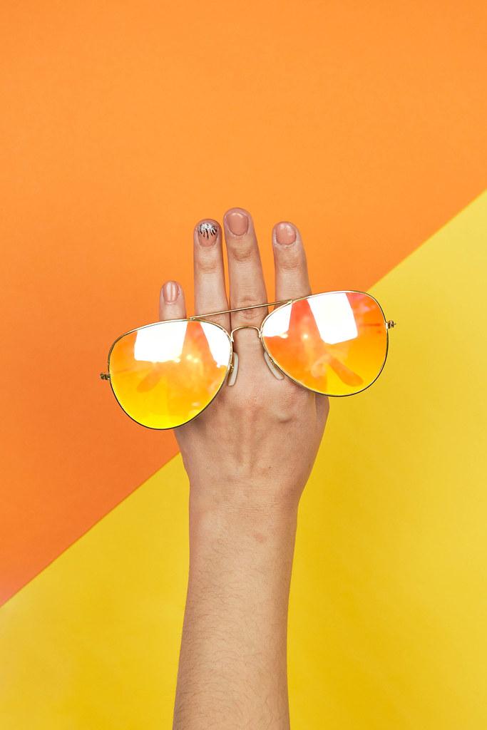 Woman hand holding bright sunglasses