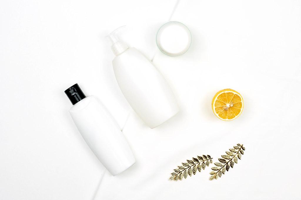 White bottles of lemon-based beauty products on white background