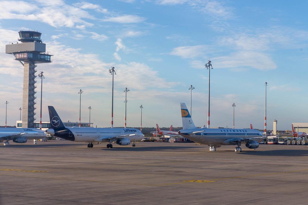 Flughafen BER: Lufthansa (im Vordergrund) und Easyjet Flugzeuge (im Hintergrund) mit Kontrollturm
