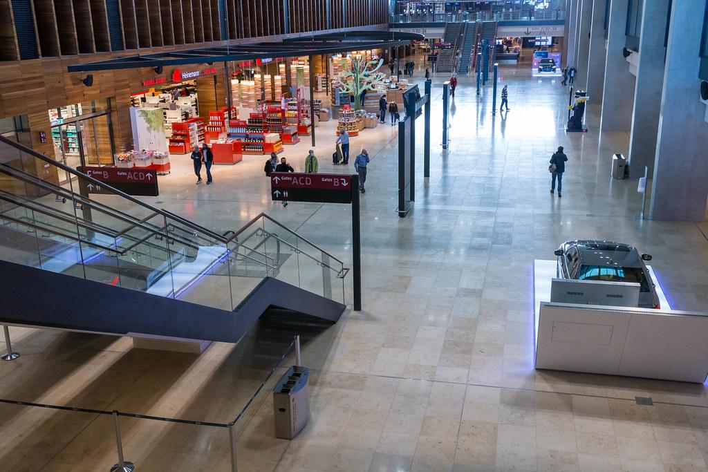 Das Terminal 1 vom neuen Flughafen BER: Heinemann Duty Free und Personen mit Mundschutz