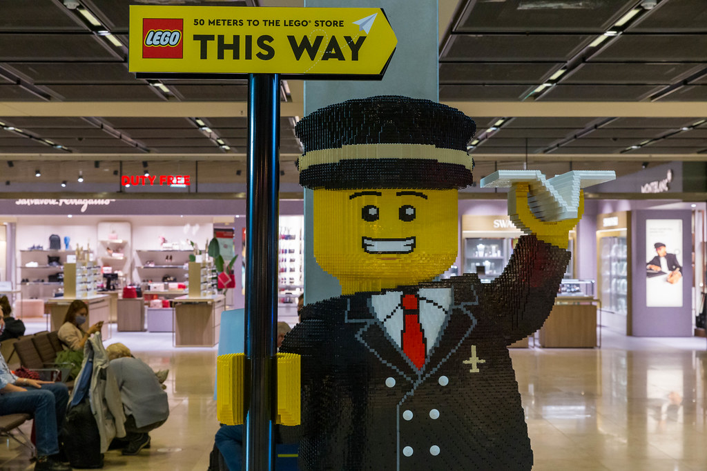 Life-size LEGO figure of airplane pilot holding a sign indicating directions to the BER airport LEGO Store