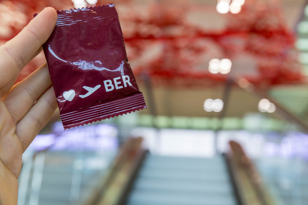Hand mit rotem Gadget des Flughafens BER vor leeren Rolltreppen und Pae Whites rotem Kunstwerk