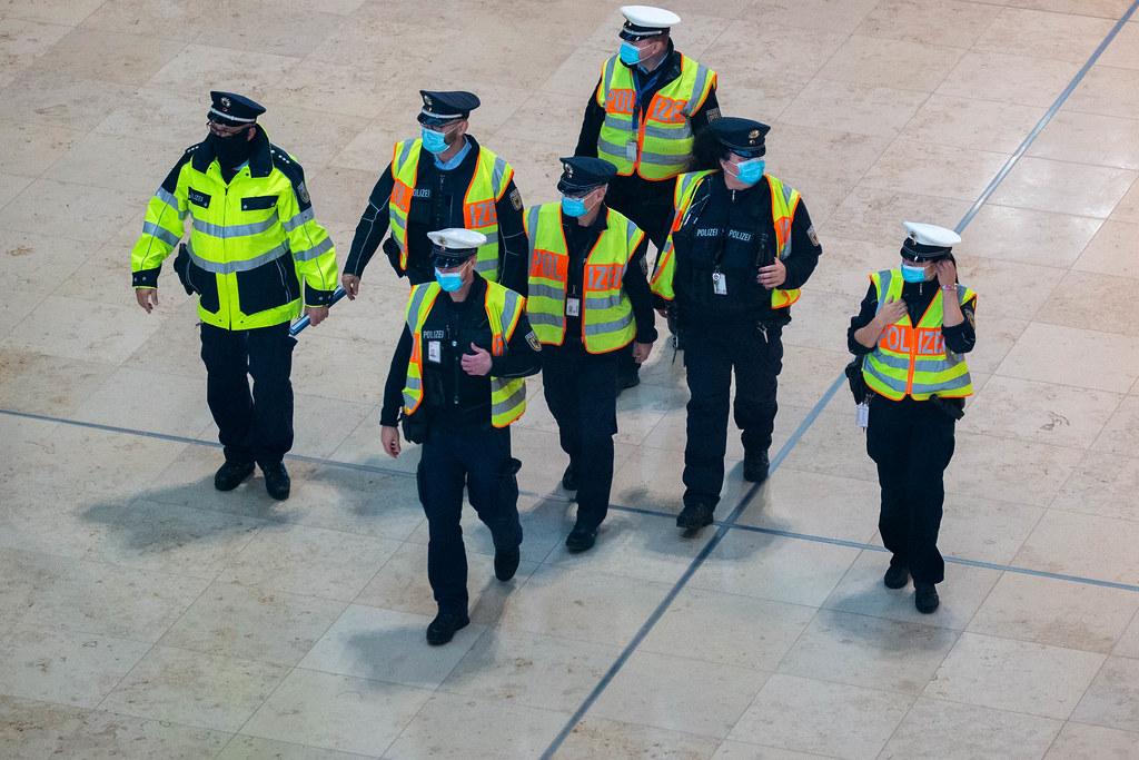 Eine Gruppe sieben Polizisten mit Mundschutz und gelber Warnweste am Flughafen BER in Berlin